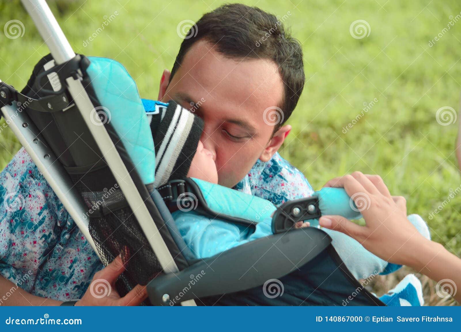 Азиатские мусульманские мать hijabi и прогулка отца через парк с сыном в прогулочной коляске пока его мама позаботить об ее todle
