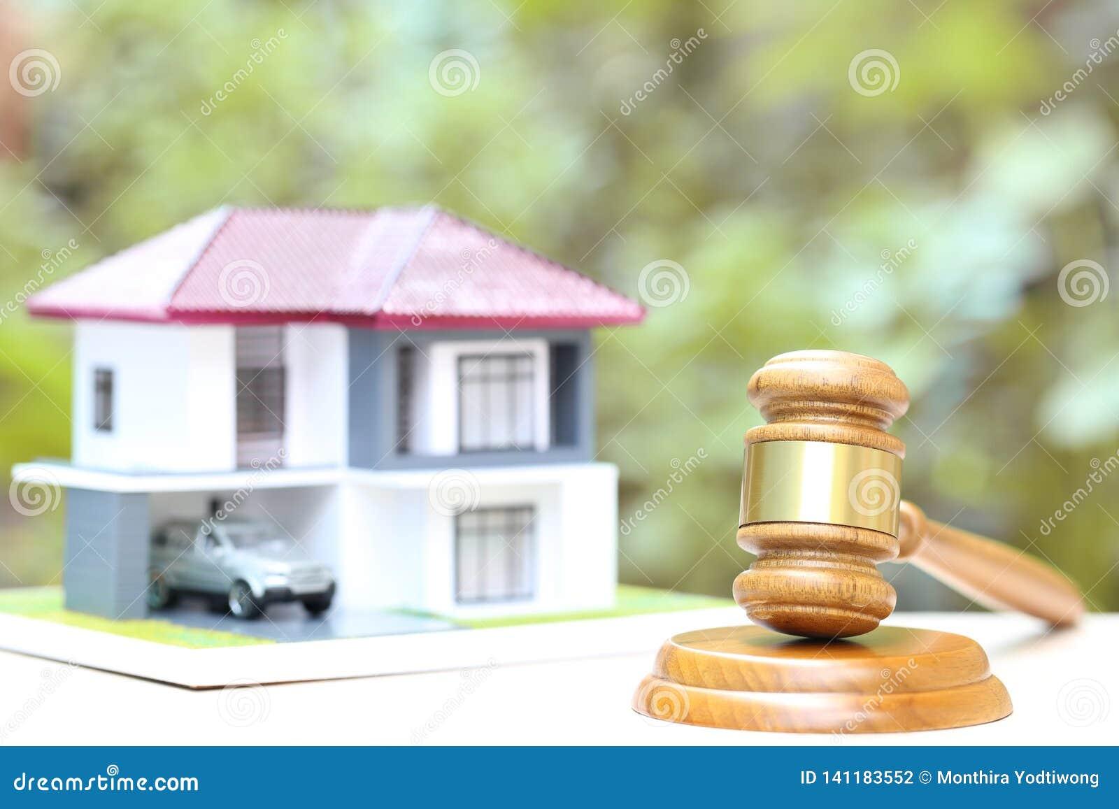 Аукцион свойства, дом молотка деревянный и модельный на естественной зеленой предпосылке, юриста домашней недвижимости и свойства
