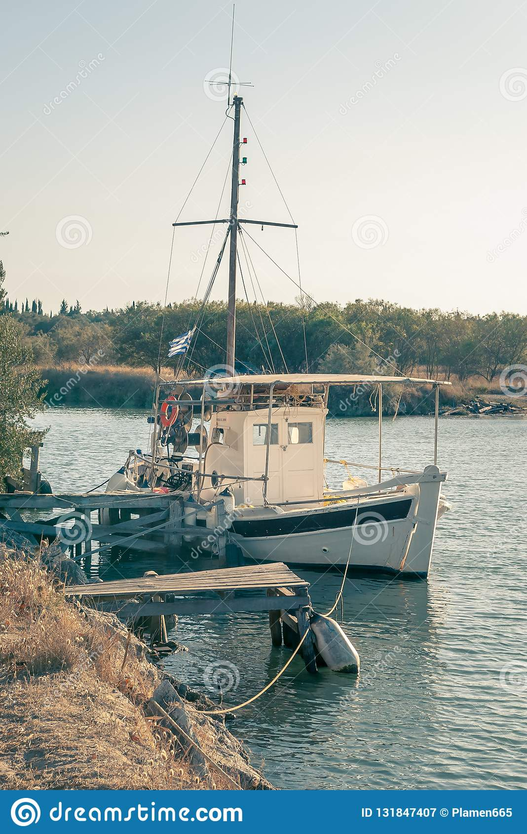A fishing boat tied to a small wooden pier .