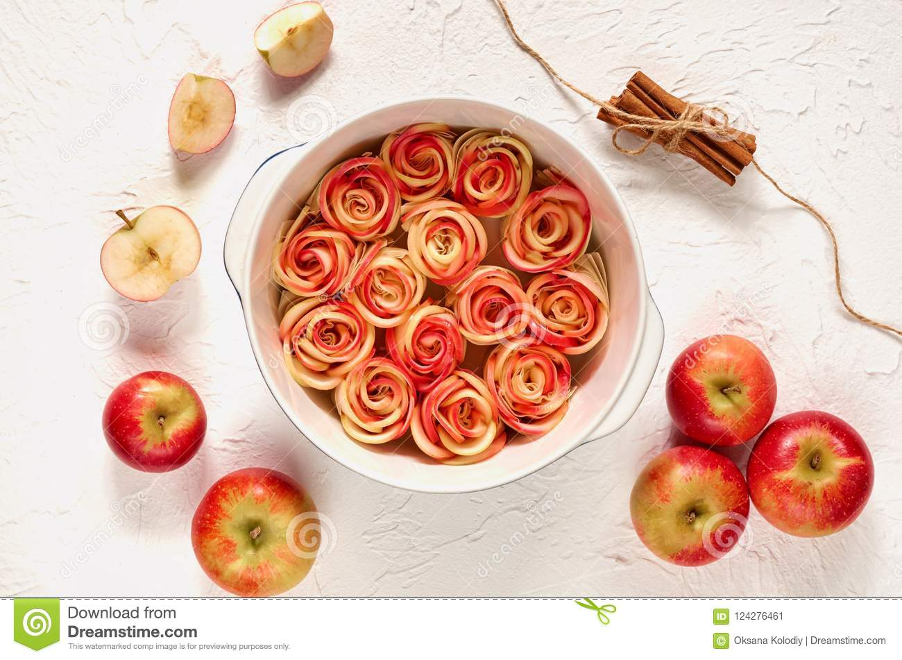 Аpple rose tart in the baking dish decorated with fresh sliced apples and cinnamon sticks. Vegetarian autumn pie on white table