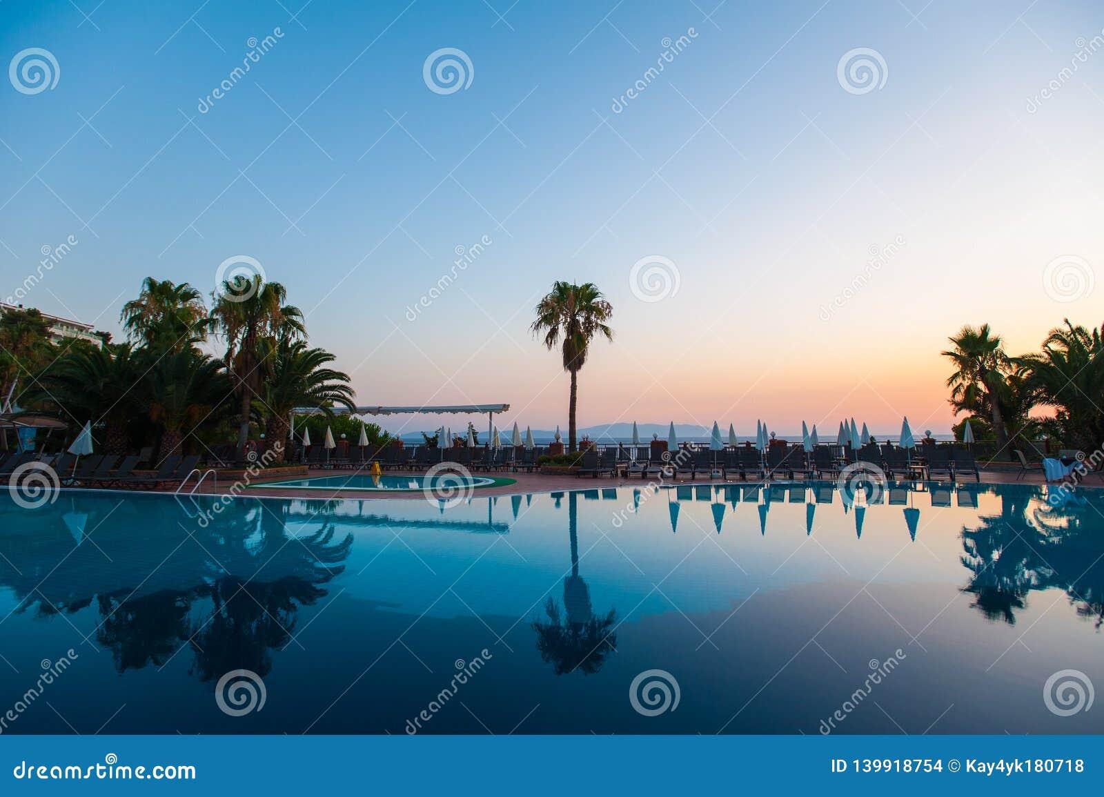 Бассейн с пальмами на заходе солнца Отражение воды