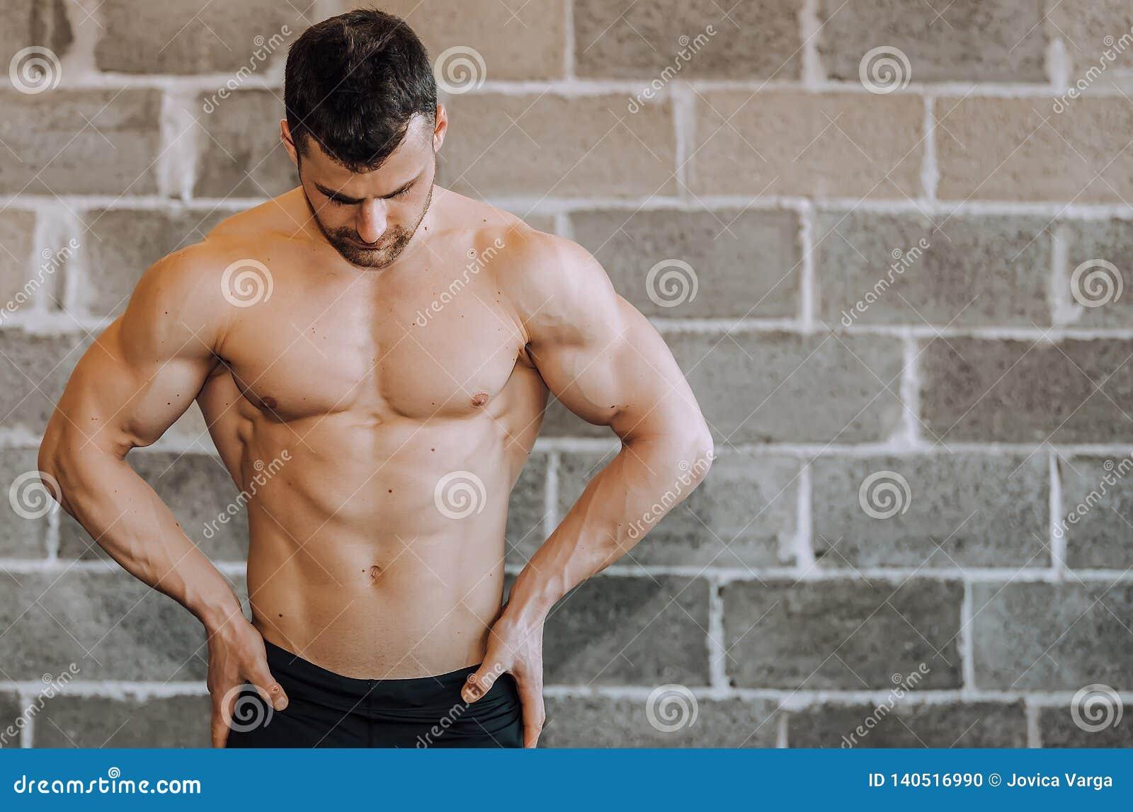 Без рубашки мышечный культурист на спортзале