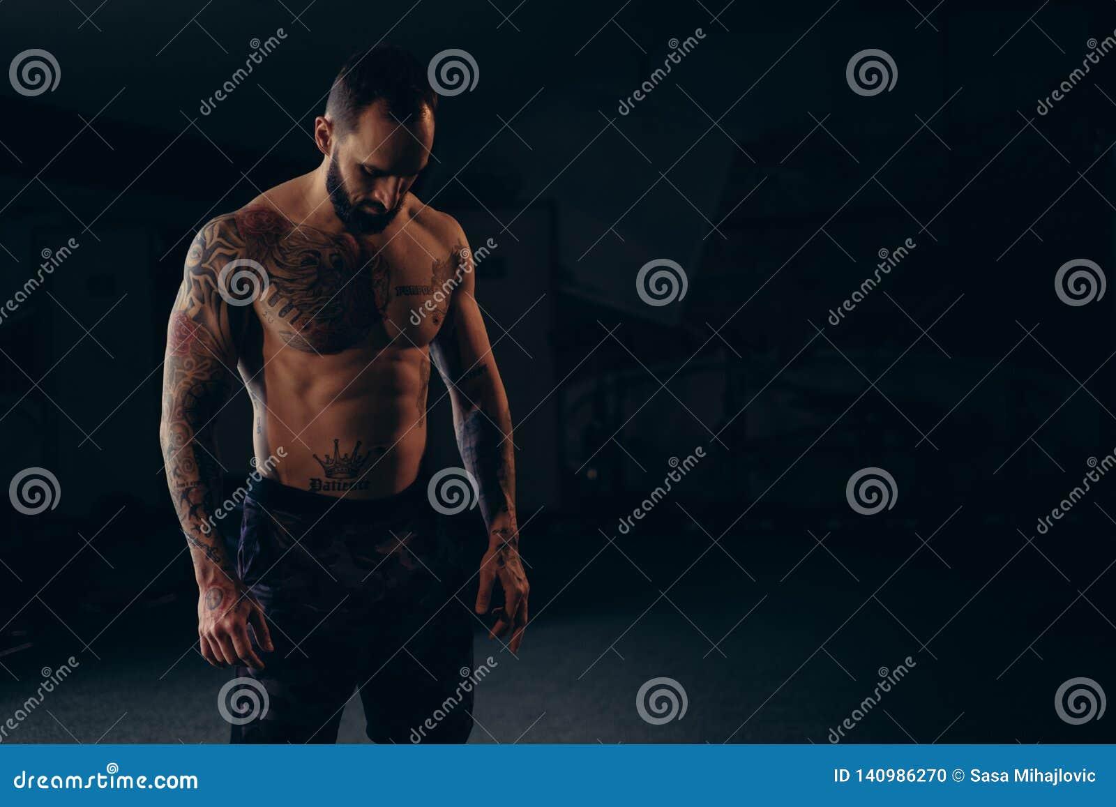Без рубашки сконцентрированный мужской спортсмен смотря на пол