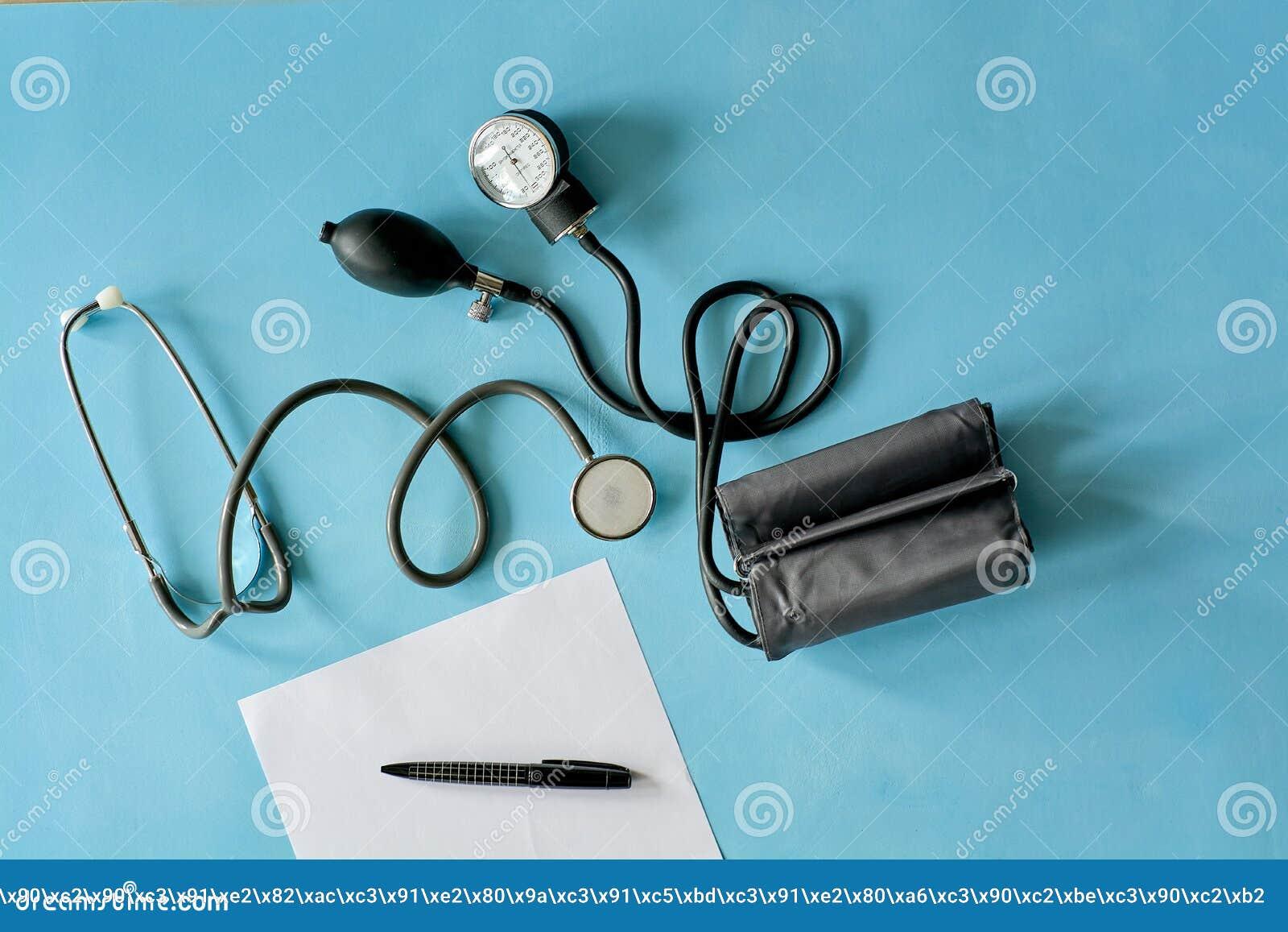 Белая бумага листа с черным стетоскопом ручки и phonendoscope, сфигмоманометром на голубой предпосылке