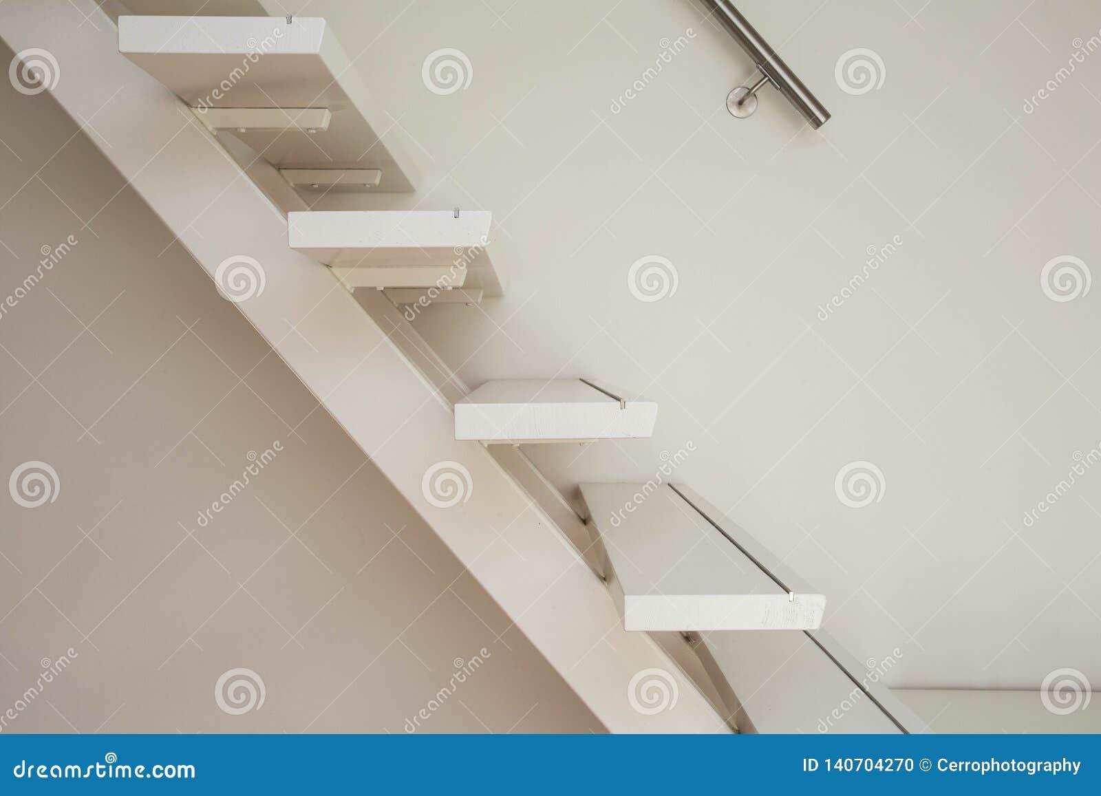 Белая современная деревянная лестница и белый конец-вверх стены