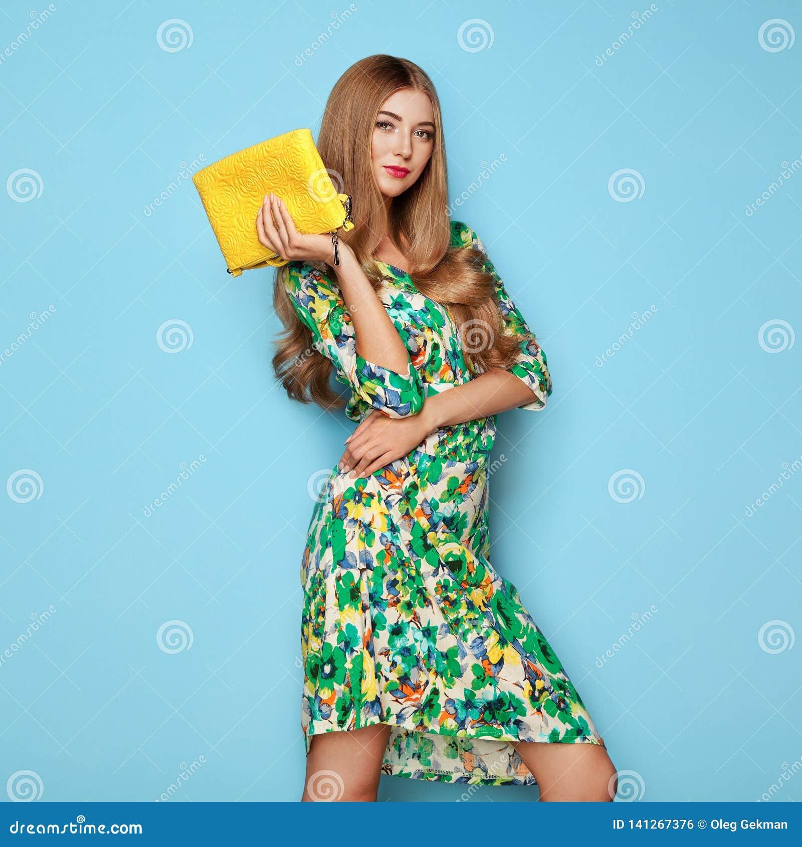 Белокурая молодая женщина в флористическом платье лета весны