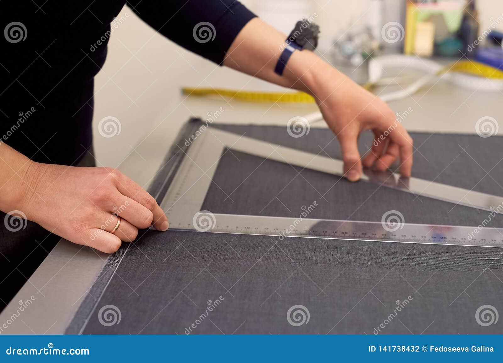 Белошвейка кладет вне ткань для резать используя дюймы Руки в съемке