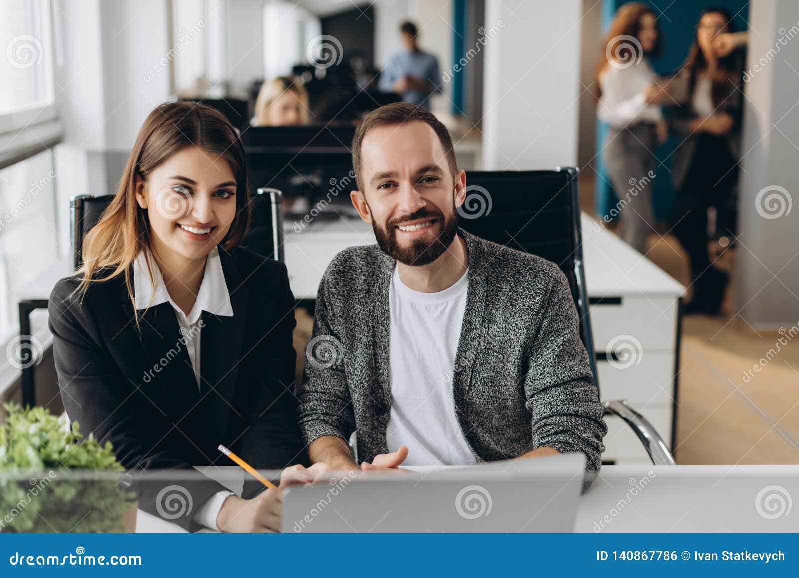 Бизнесмен и коммерсантка работая с компьтер-книжкой на современном офисе