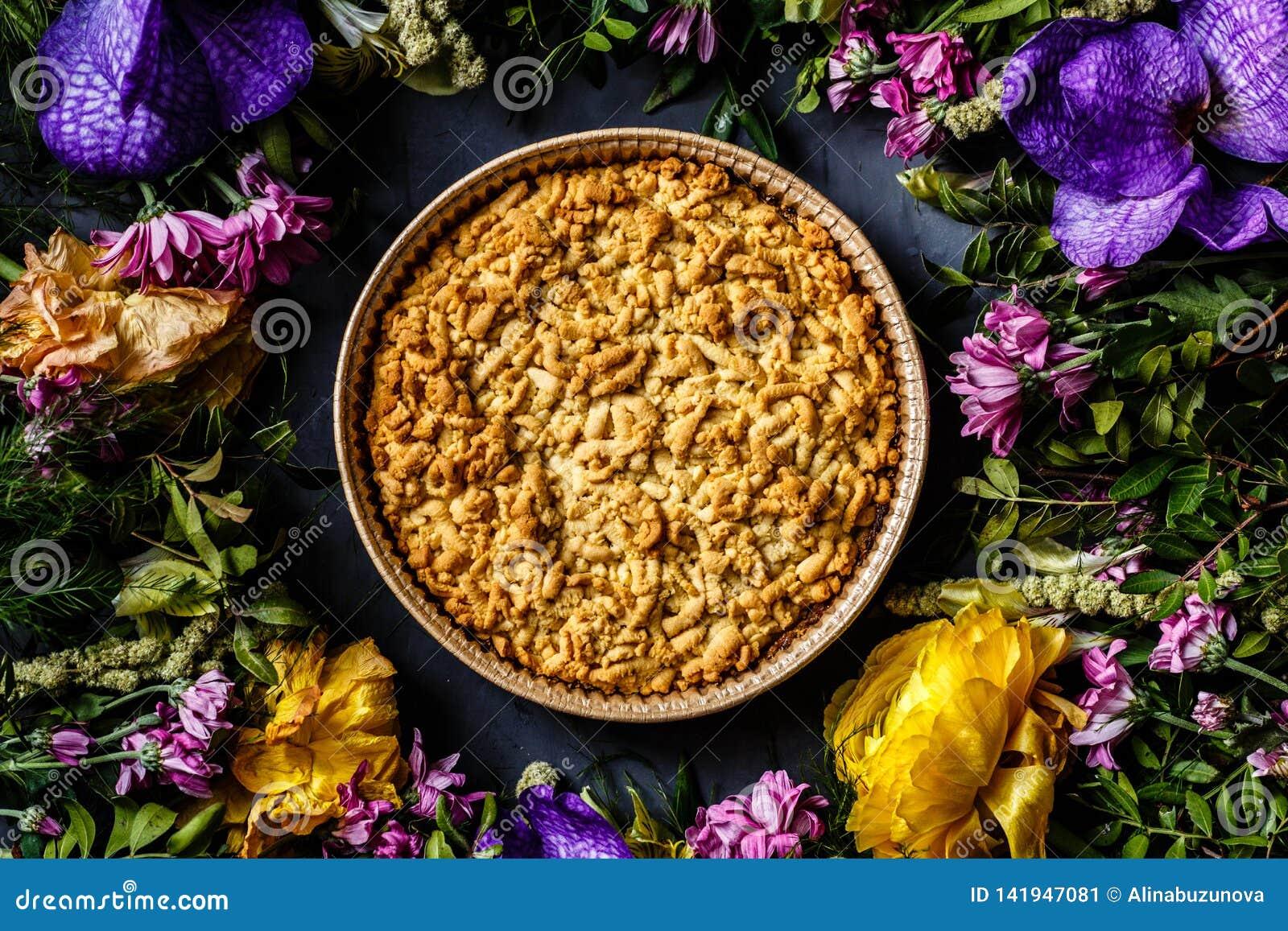 Букет ярких цветков и яблочного пирога лежа на серой предпосылке Плоское положение Взгляд сверху
