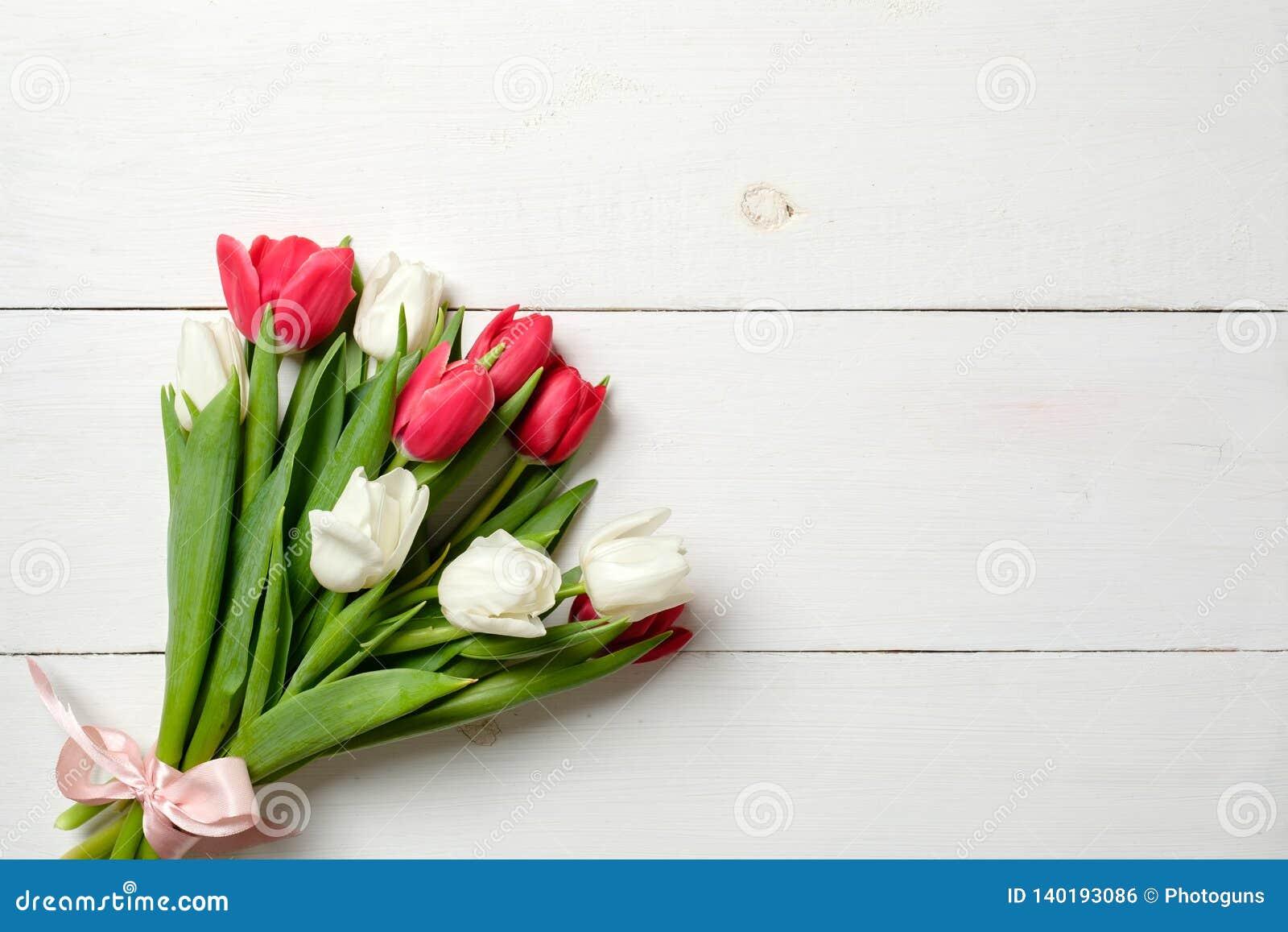 Букет тюльпанов на белом деревянном столе, космосе экземпляра для текста Модель-макет на праздники весны, Inte знамени приглашени