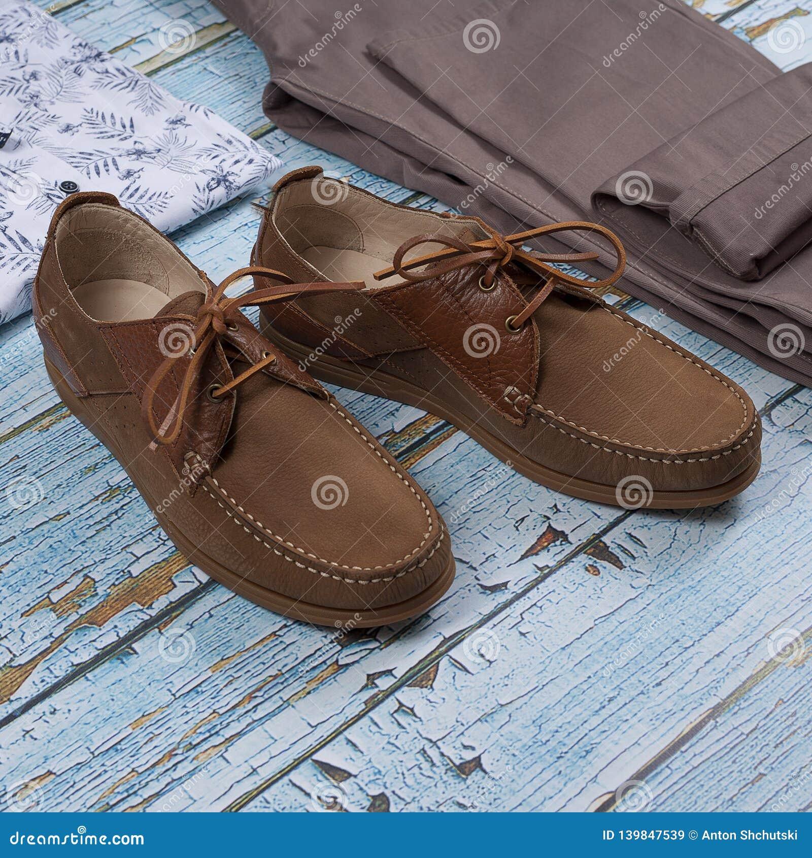Ботинок, пояс, брюки и рубашка loafer Брауна изолированные на деревянной предпосылке Взгляд сверху