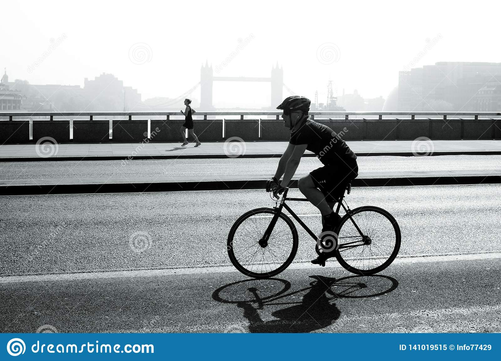 Велосипедист и jogger на мосте Лондона, Лондоне, Великобритании