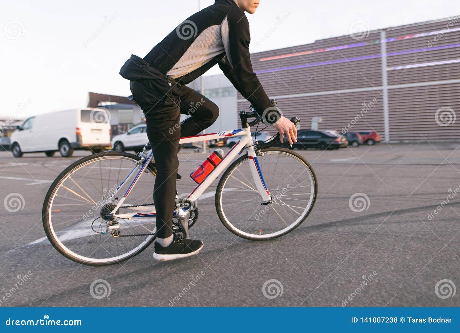 Велосипедист на быстро развивающийся езде велосипеда, езда в парковке, на предпосылке торгового центра