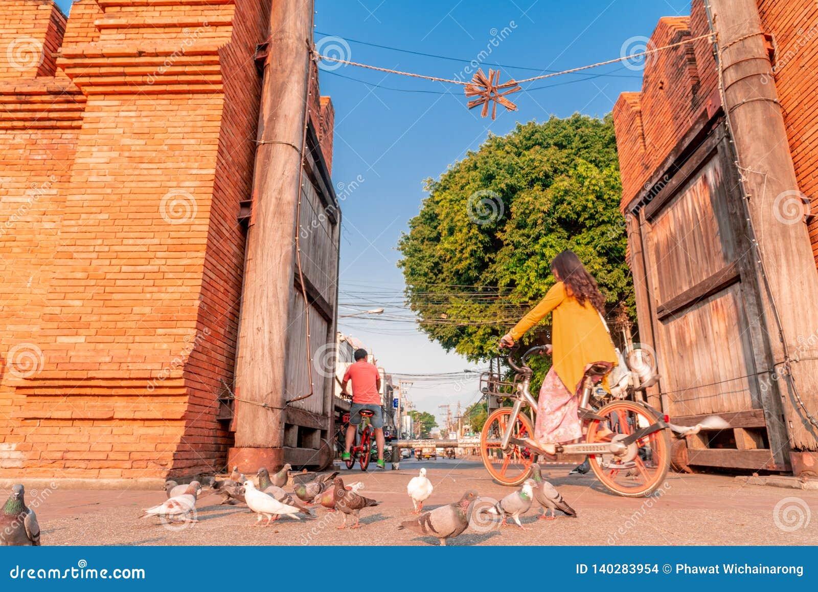 Велосипеды езд туристов на воротах Thapae в городе Чиангмая