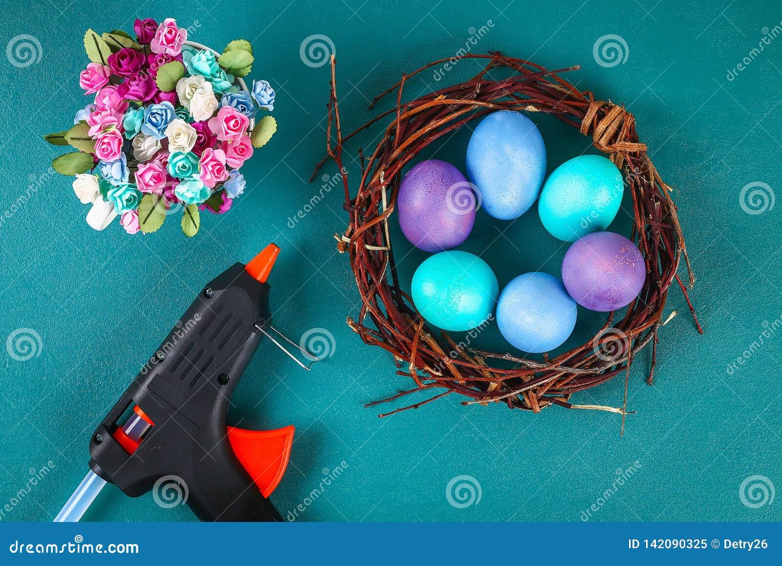 Венок Diy пасхи хворостин, покрашенных яя и искусственных цветков на зеленой предпосылке
