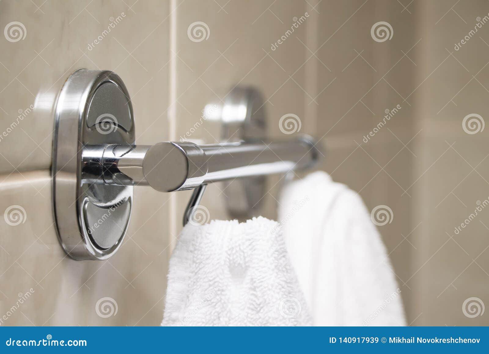 Вешалка с белыми полотенцами висит на стене