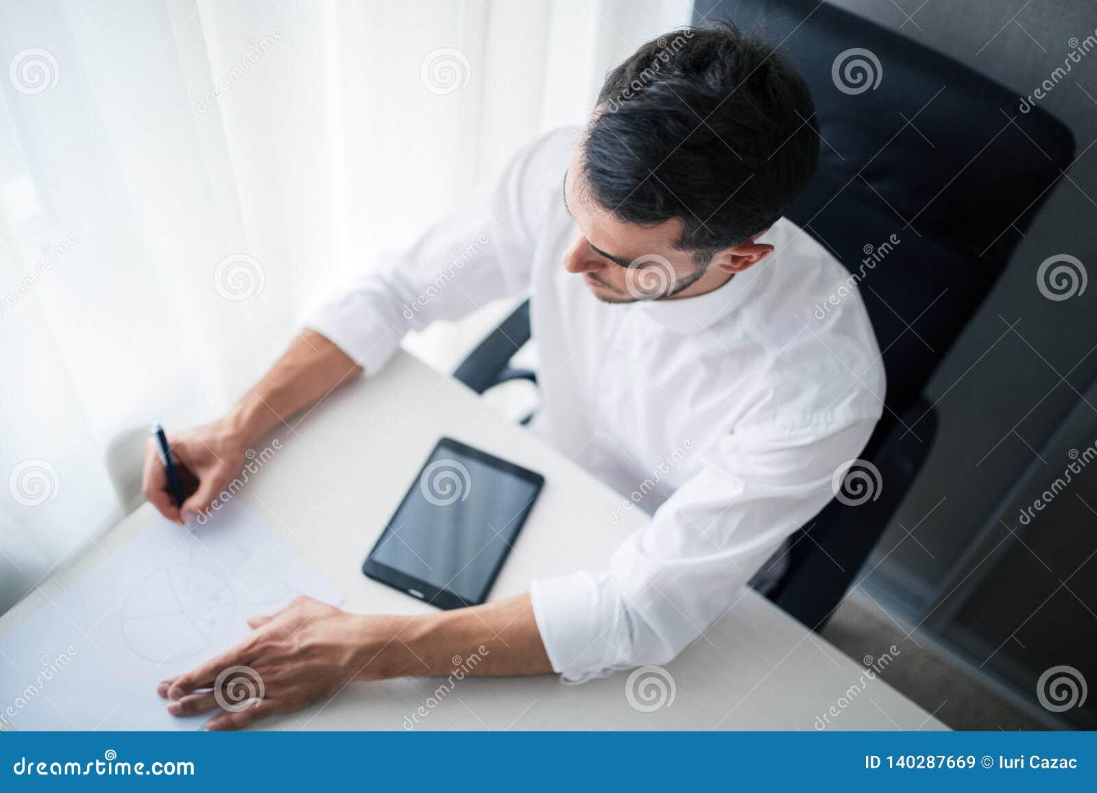 Взгляд сверху бизнесмена работая на приборе, устройства в офисе, сидя на стуле смотря спуск и запись