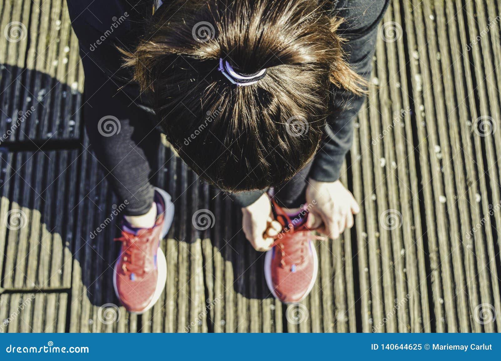 Взгляд сверху молодой женщины фитнеса связывая шнурки, готовый для того чтобы пойти побежать