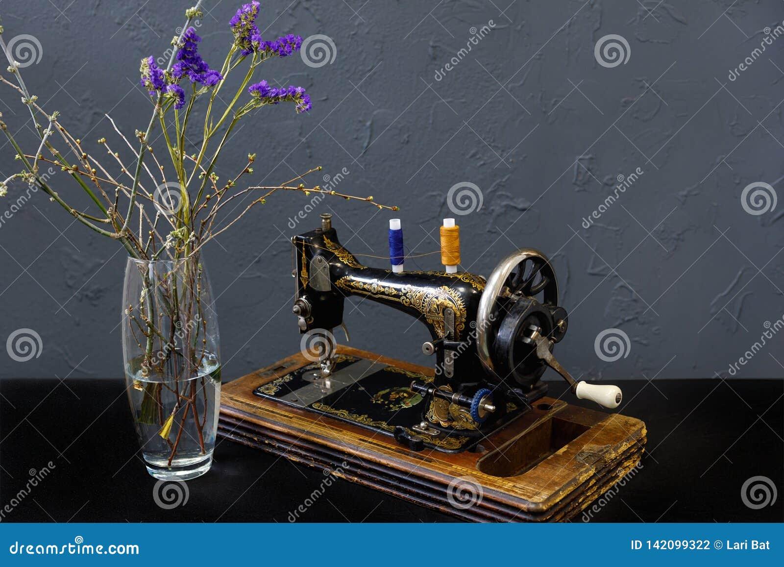 Винтажная швейная машина ваза с голубыми цветками
