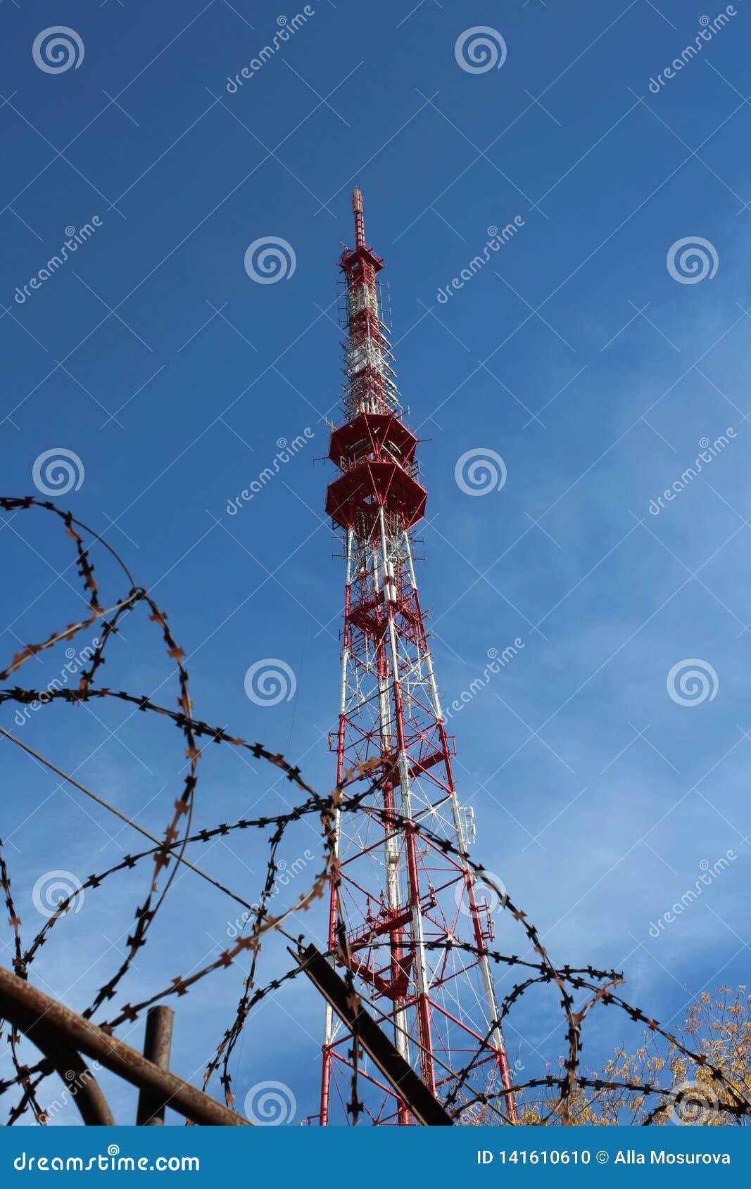 Высокая антенна радио ТВ со спутниковым сигналом за загородкой колючей проволоки против голубого неба