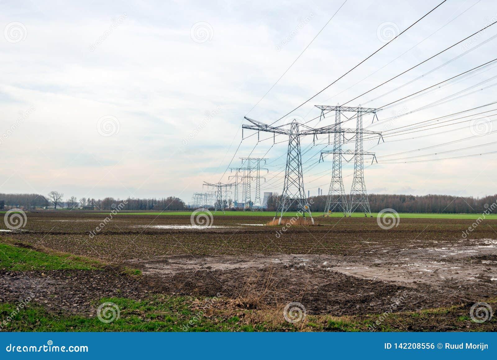 Высоковольтные опоры и линии высокого напряжения для транспортировать электричество от электростанции на заднем плане