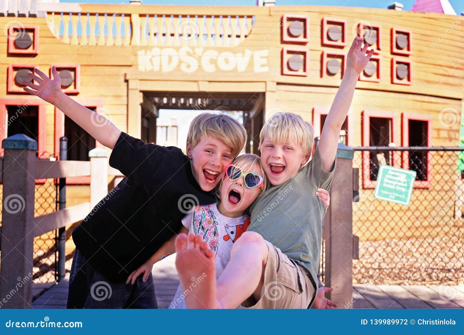 Группа в составе счастливые, усмехаясь дети снаружи на парке на летний день