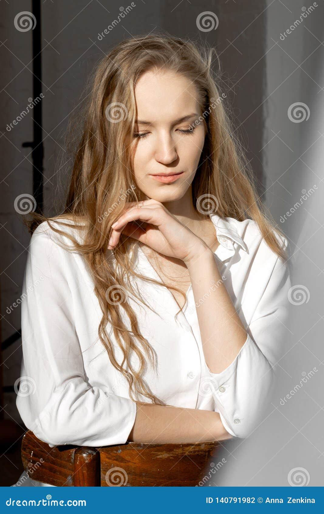 Грустная внимательная модель смотря вниз в белой рубашке