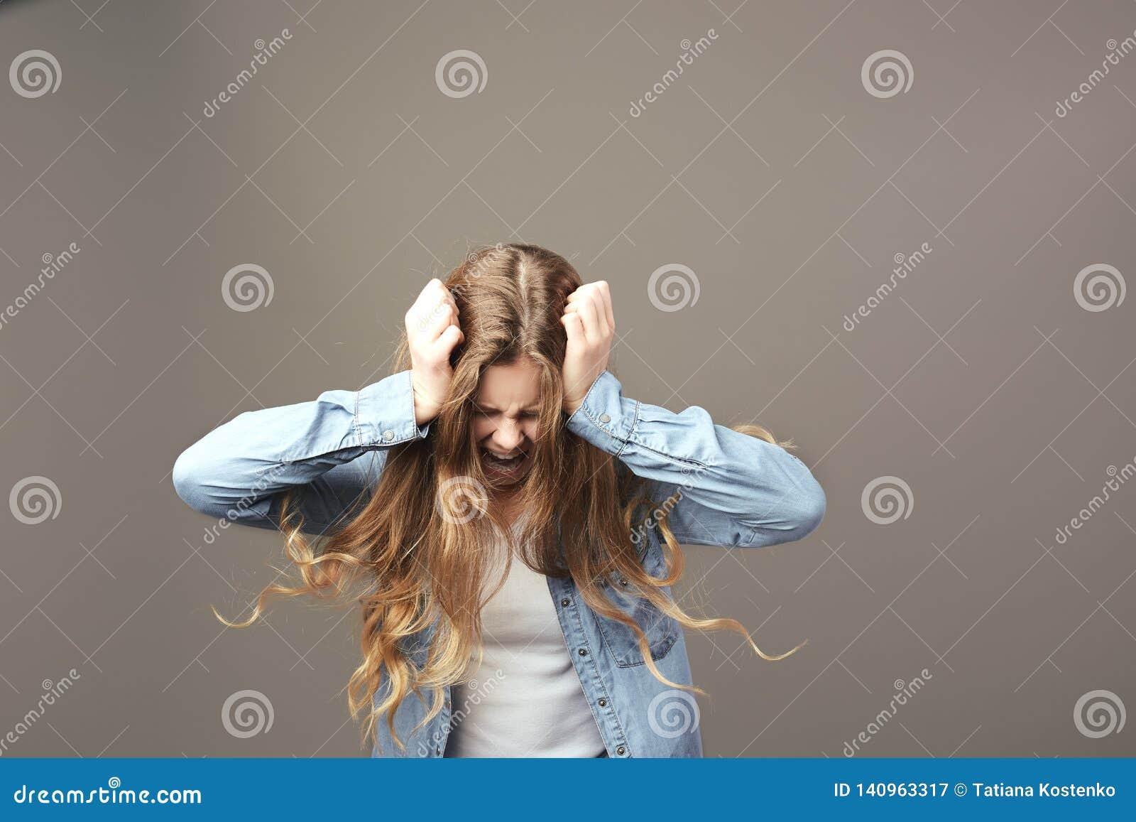 Грустная коричнев-с волосами девушка одетая в белых футболке и демикотоне держит ее руки на ее голове и окриках на серой предпосы