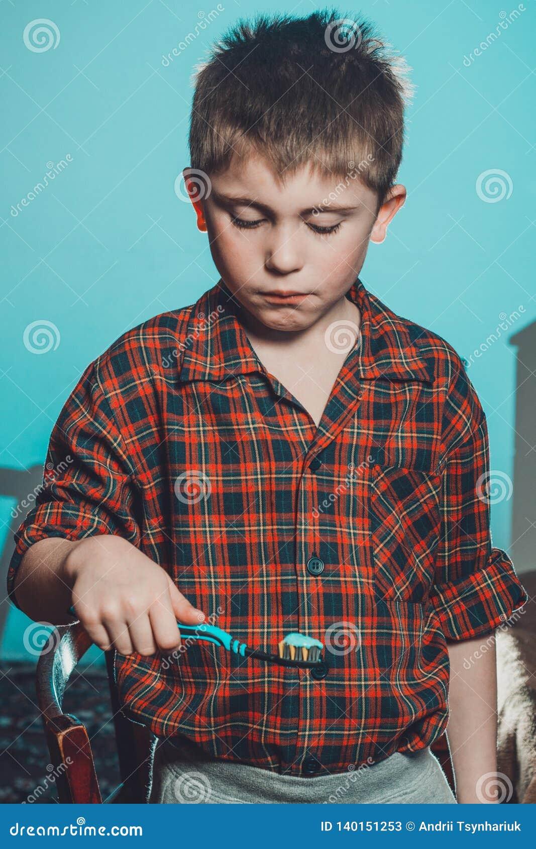 Грустный мальчик в пижамах не силен для того чтобы почистить его зубы щеткой перед идти спать на голубой предпосылке