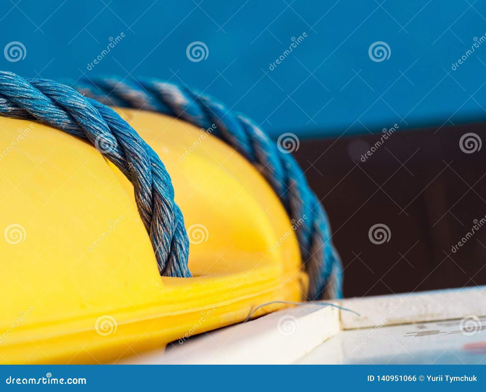Голубая переплетенная веревочка на желтое lifebuoy, макрос, мелкий dept поля