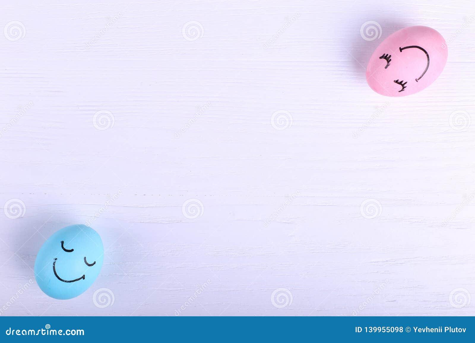 Голубые и розовые яйца на таблице, космосе экземпляра Счастливый дизайн поздравительной открытки концепции пасхи