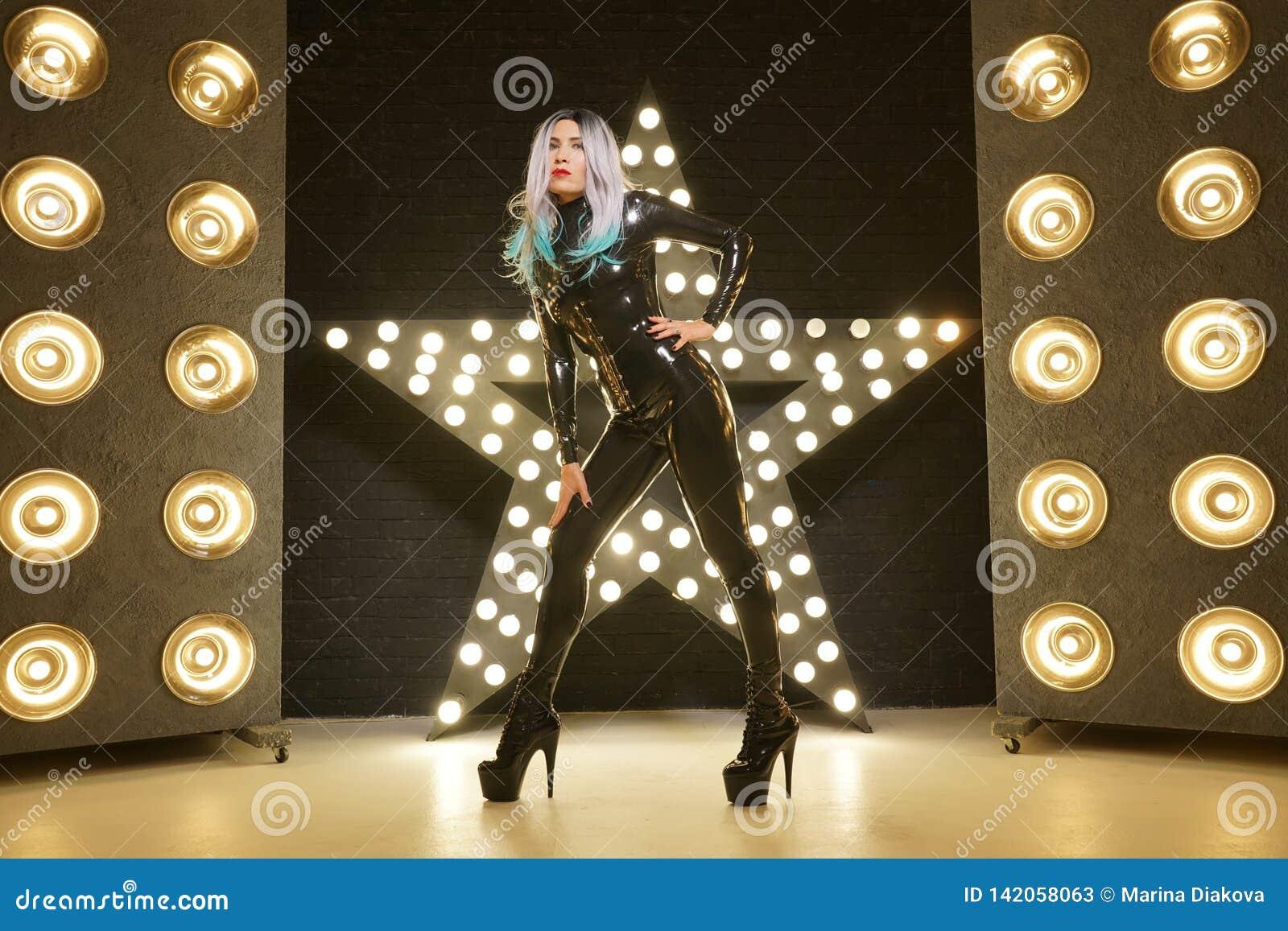 Горячая тонкая женщина представляя в одеждах моды латекса резиновых на черной предпосылке с шариками желтых светов