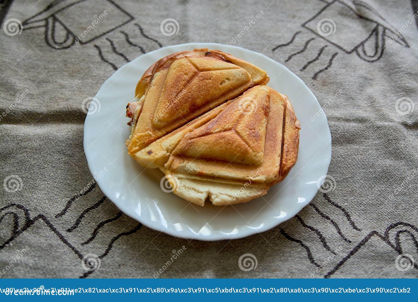 Горячий хрустящий сэндвич Свежий горячий хрустящий очень вкусный тостер на белой плите на завтрак