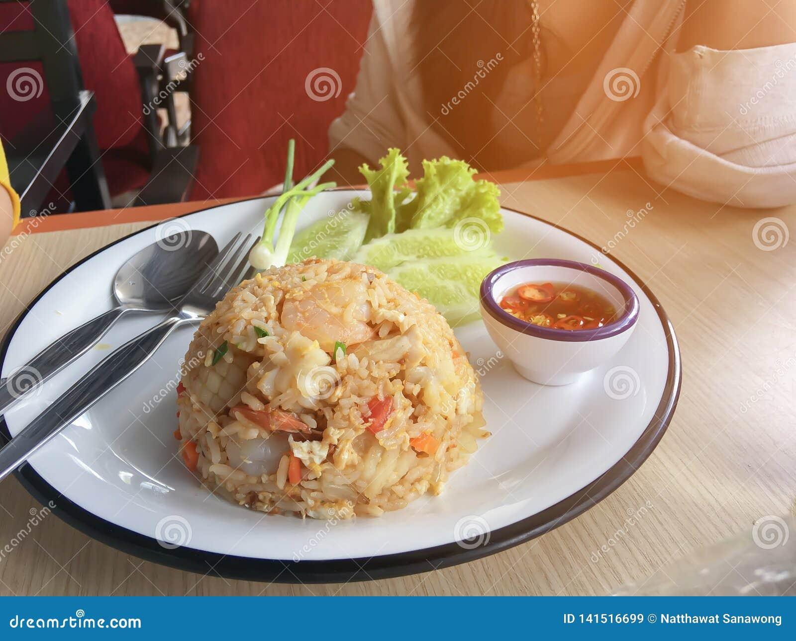 Жареные рисы с креветкой на тайском украшают блюдо с зеленым луком, огурцом, салатом, чилями и лимоном