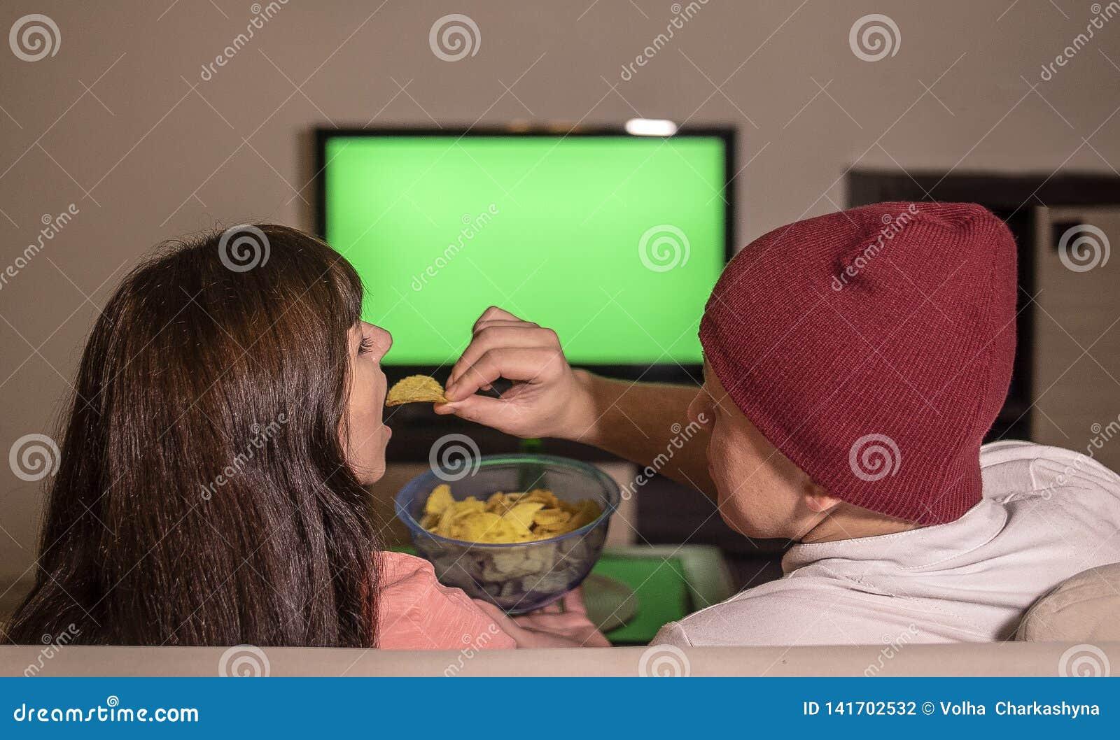 Женатая пара сидит дома на софе в вечере, смотрит ТВ и ест обломоки
