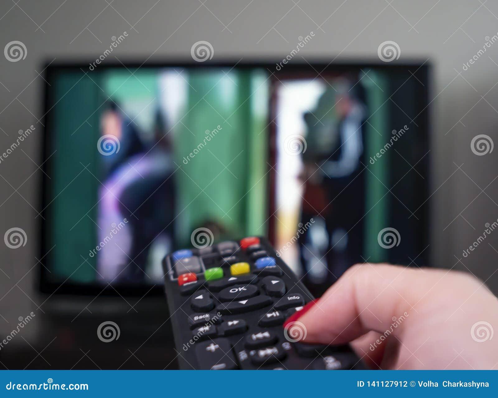Женская рука с дистанционным управлением на предпосылке ТВ