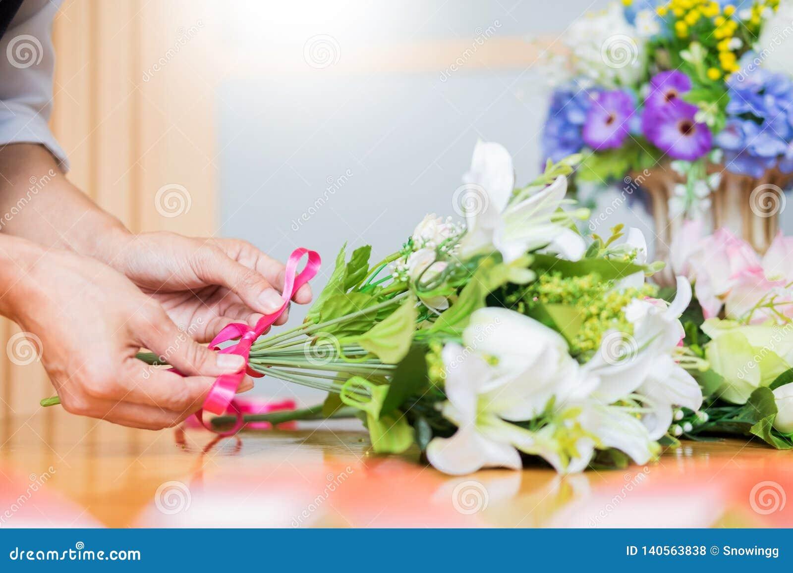 Женский флорист на работе используя аранжировать делая красивый искусственный жилет букета на цветочном магазине, деле, продаже и