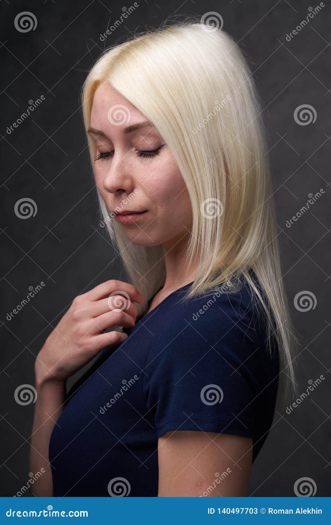 Женщина красоты белокурая в черных случайных одеждах на серой предпосылке