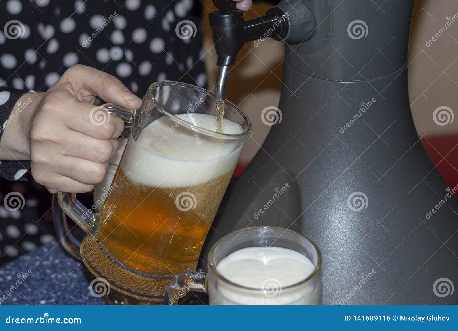 Женщина льет свежее холодное пиво от распределителя столешницы охлаждая в стекла пива
