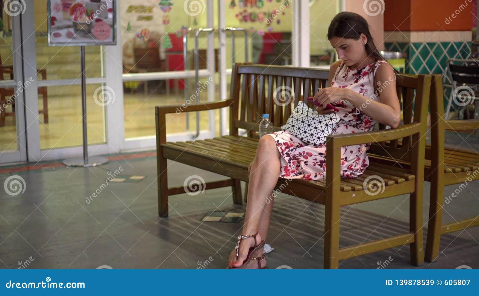Женщина получает сообщение и принимает телефон для того чтобы прочитать ее усмехаясь