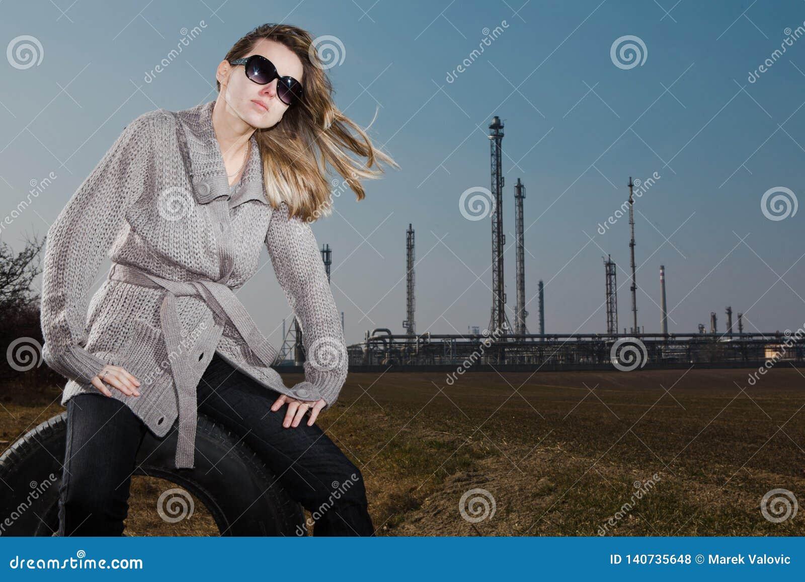 Женщина сидя на используемой автошине - естественная кожа без ретуширует