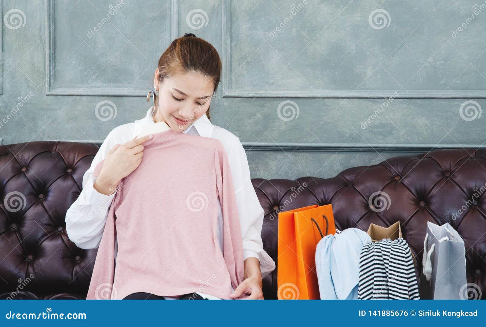 Женщина сидя на софе она держит розовую рубашку и усмехается