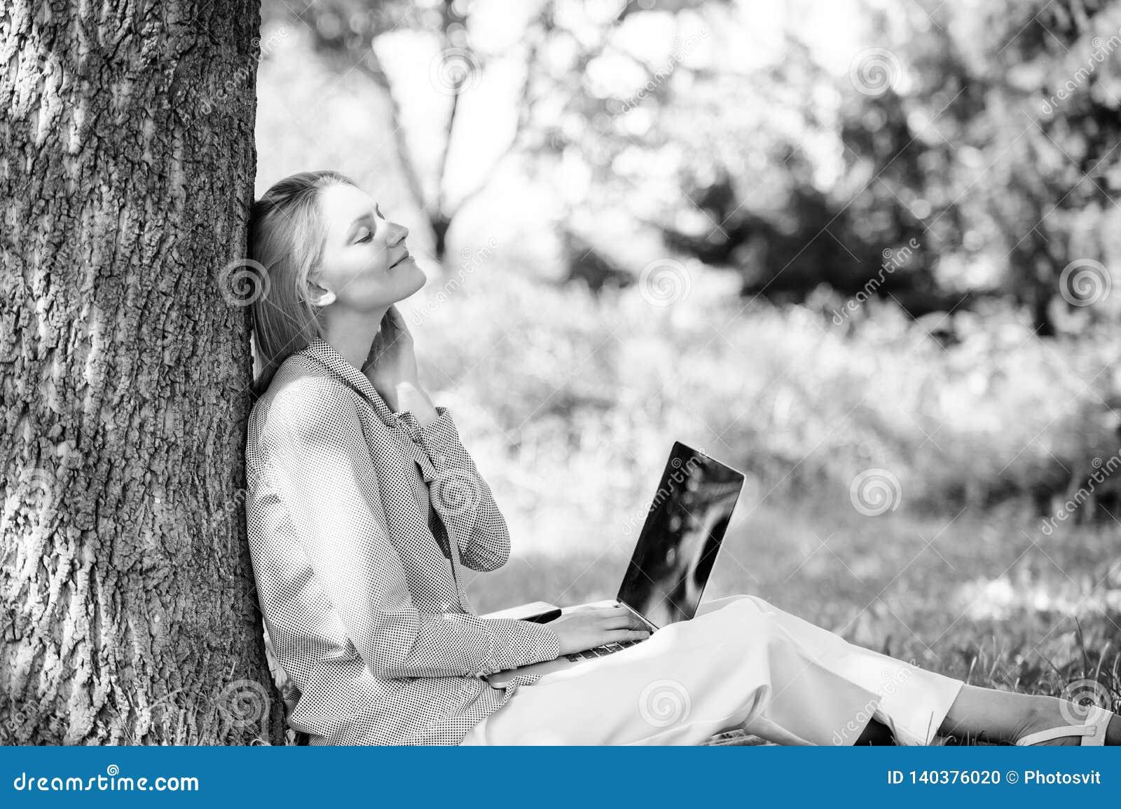 Женщина с ноутбука работы деревом outdoors постным Минута для ослабляет Технология образования и концепция интернета Работа девуш