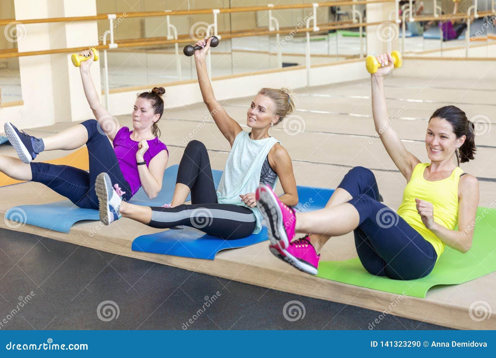 Женщины делая тренировки гантели на разминке группы в фитнес-зале