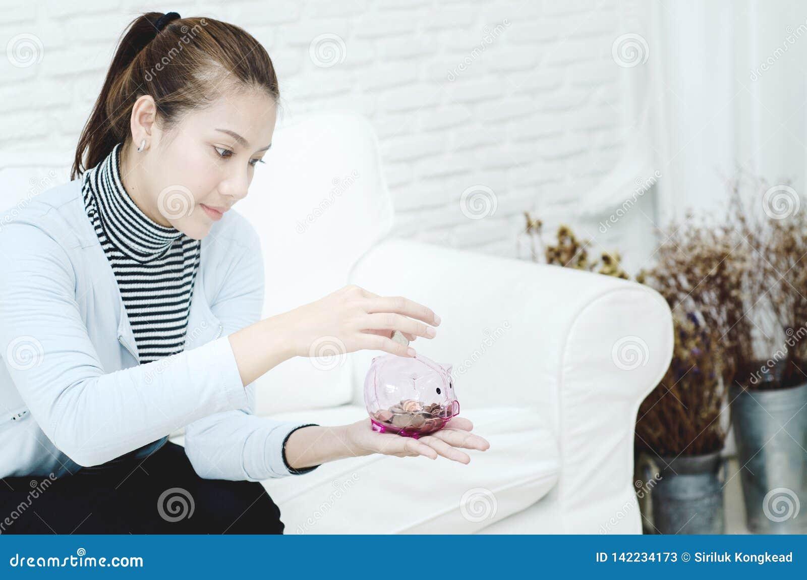 Женщины усмехаясь и розовый опарник монетки в руке