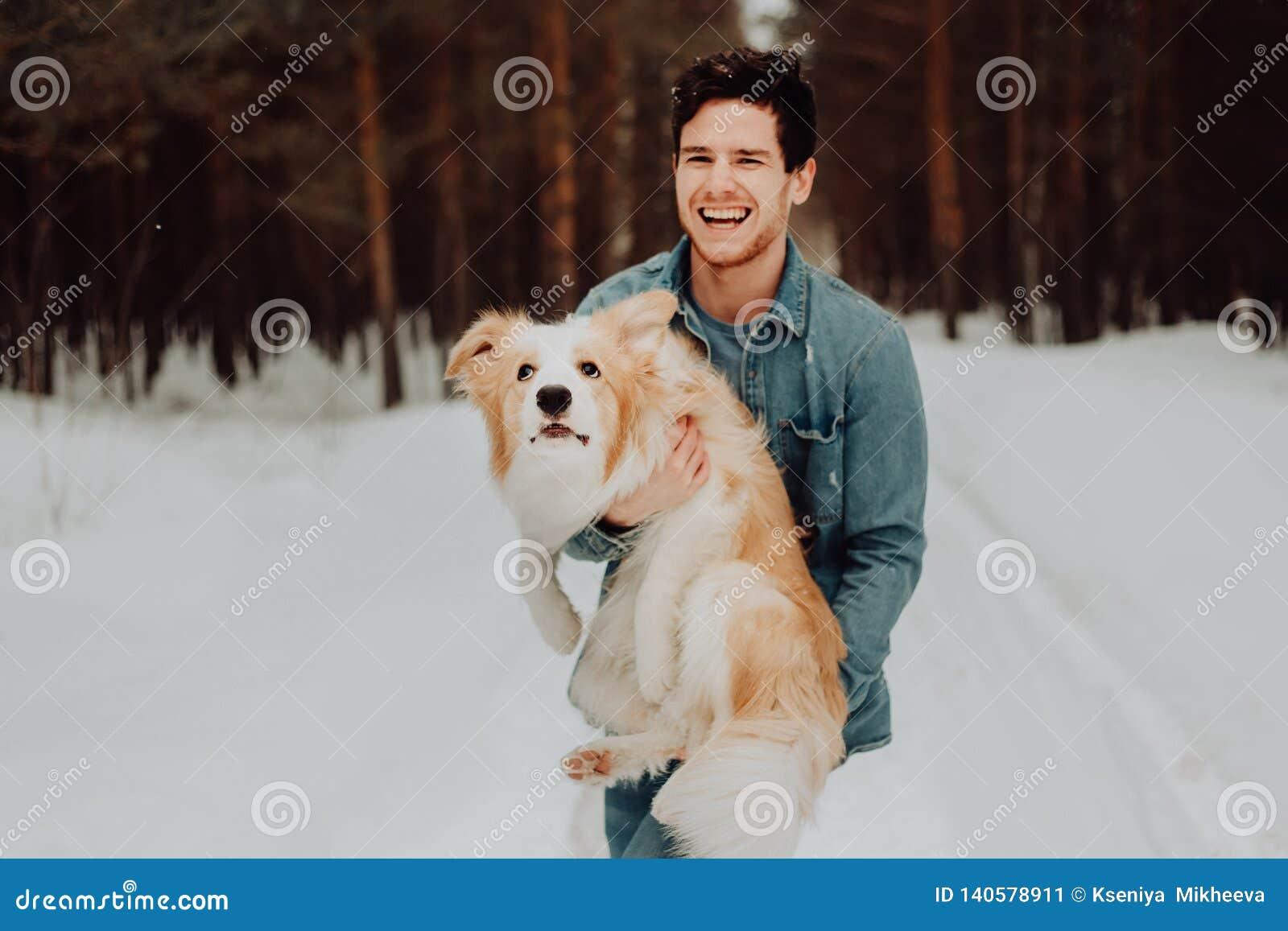 Жизнерадостный милый смеясь и усмехаясь парень в одеждах джинсов с красным цветом Коллиы границы собаки на его руках в снежной ко