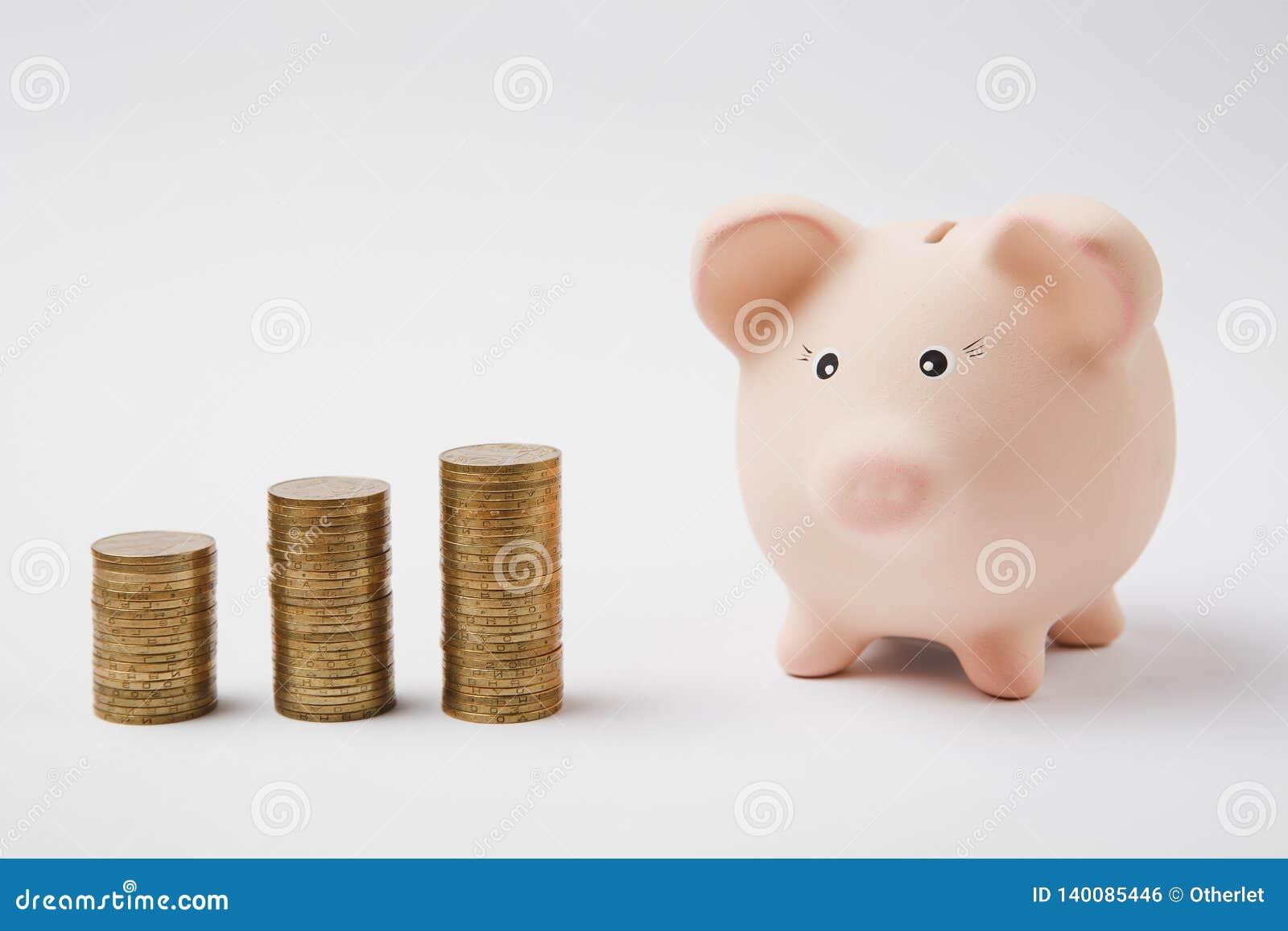 Закройте вверх розового piggy банка денег, стогов золотых монеток изолированных на белой предпосылке стены Накопление денег