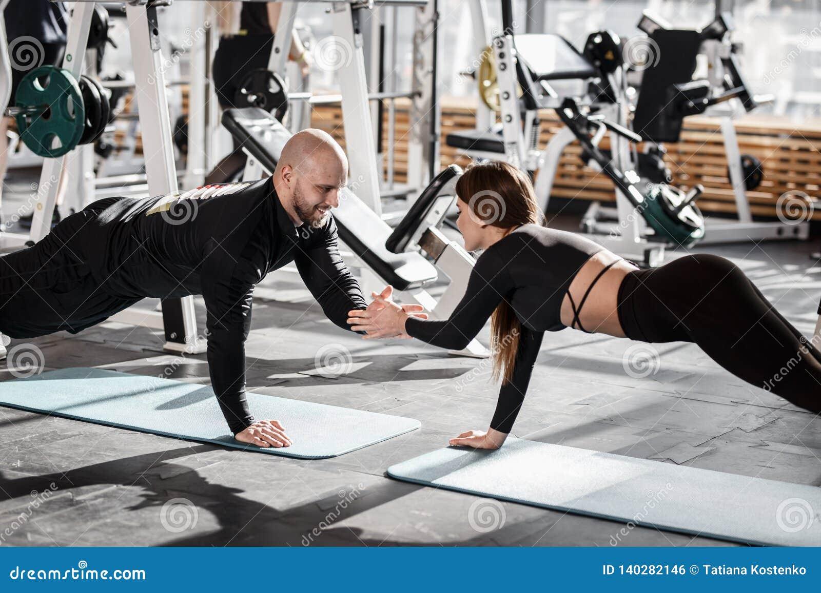 Зверский атлетический человек и молодая худенькая девушка одетые в черных одеждах видов делают планку держа рука об руку в