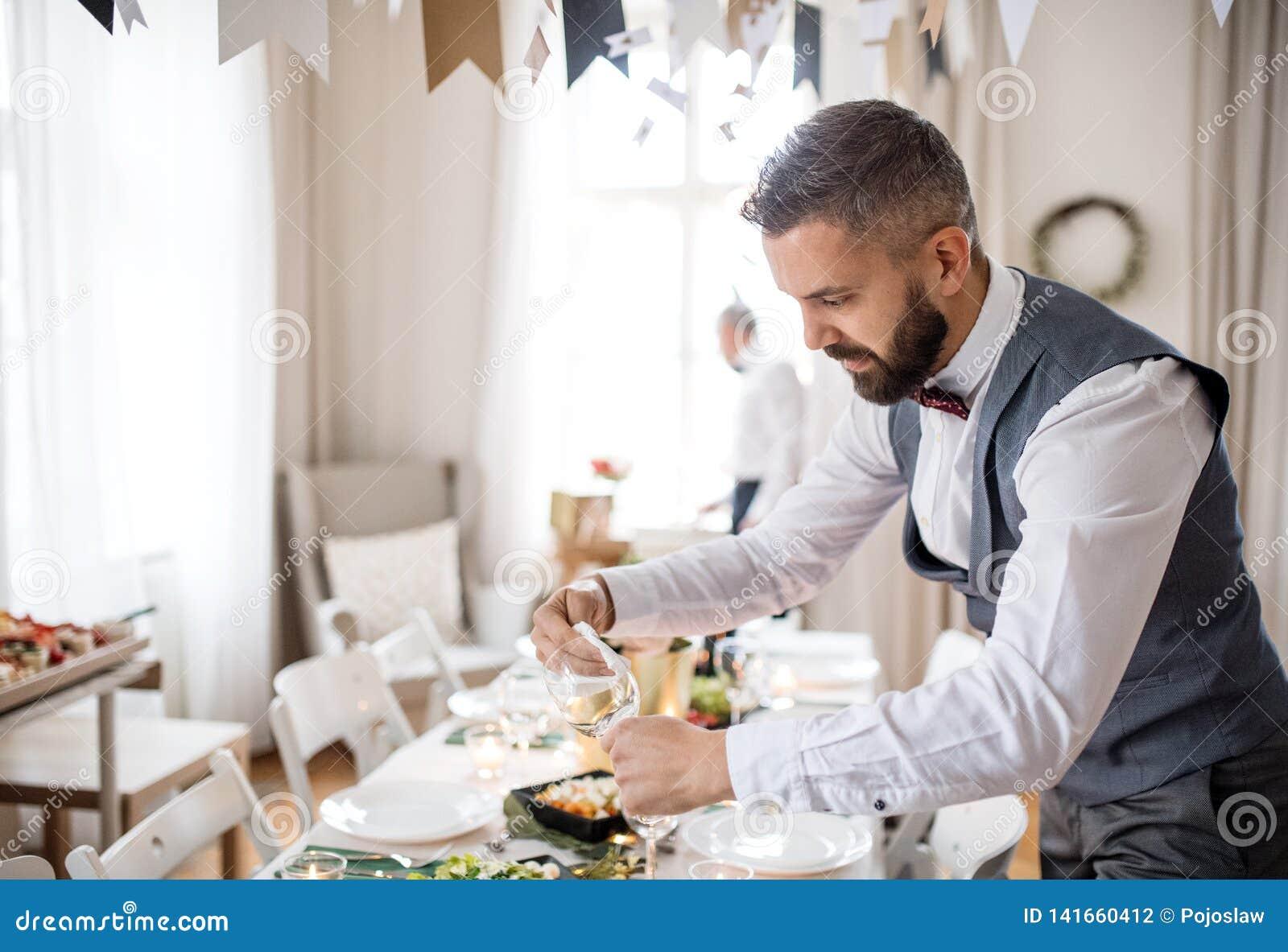Зрелый человек со смычком и жилет устанавливая таблицу для крытой партии