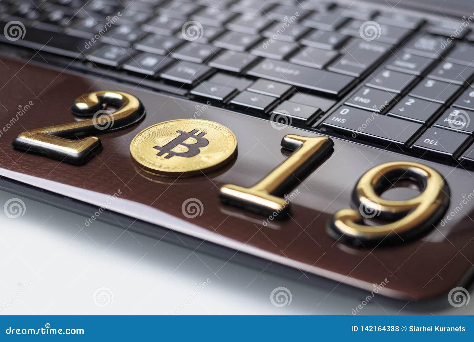 золотое bitcoin оно лежит на ноутбуке Надпись 2019 Тонизировать
